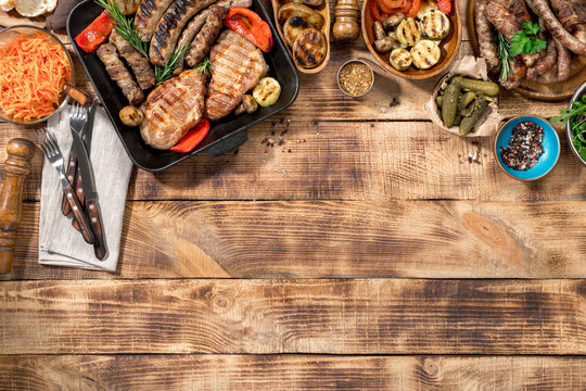 Different foods cooked on the grill on the wooden table