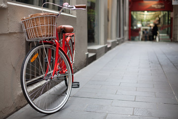 A red bicycle parked in a laneway