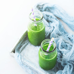 Healthy food concept green smoothie breakfast on white gray tray blue textile. Fruit vegetable juice glass bottle