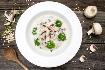 Soup with Fresh Mushrooms and Raw Ingredients on Wooden Background