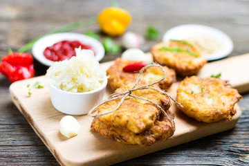 Fried Potato Pancakes on Breadboard with Ingredients on Wooden Background