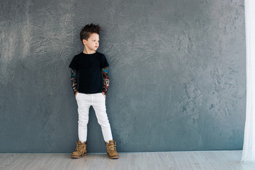 Little fashionable boy on the background of gray walls.