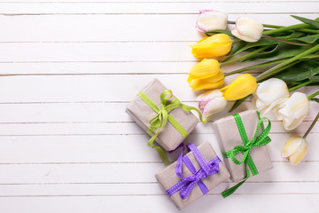 Bright yellow  spring tulips and box with presents on white  woo