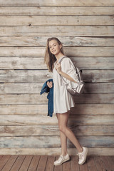 Fashion lifestyle portrait of young pretty woman in wooden room