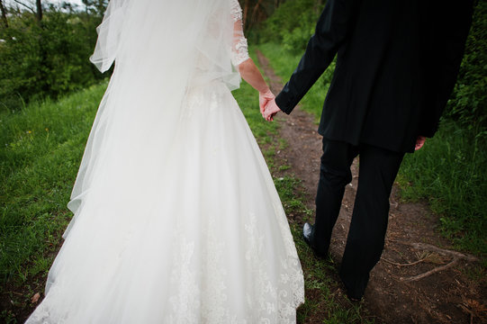 Walking newlyweds holding hand at park at their wedding day.