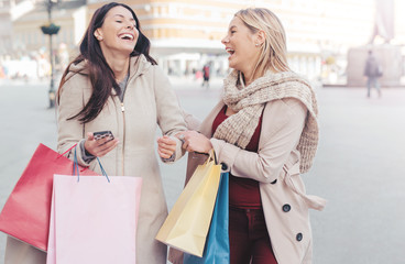 Shopping time. Two beautiful girls walking down the street on a
