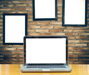 Computer notebook on brick wall background with advertise frame