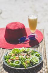 Seafood salad, orange fresh juice, hat and sunglasses on the table near sea