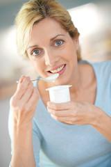 Portrait of blond woman eating yogurt