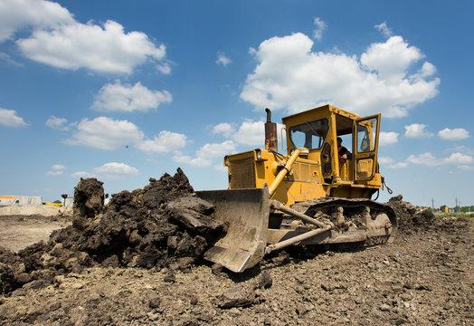Bulldozer moving earth on sunny day