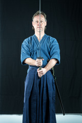 Adult caucasian male training Iaido holding a Japanese sword with focused look. Studio shot with black background.