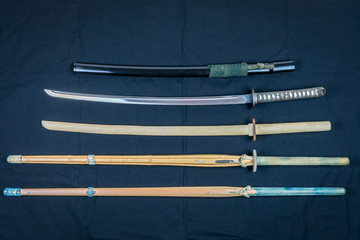 A collection of weapons for training, equipment for Japanese sport Iaido and Kendo. Wood, bamboo and steel sword arranged and displayed on black background.
