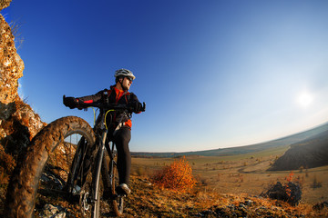 low angle view of cyclist standing with mountain bike against bright sun and blue sky.