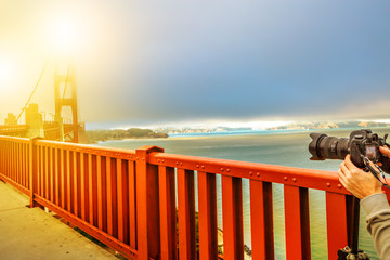 Camera taking a shot of Golden Gate Bridge and red railing, San Francisco, California, United States. Pedestrians perspective of bridge.Concept of hobbies, travel, tourism and professional photography
