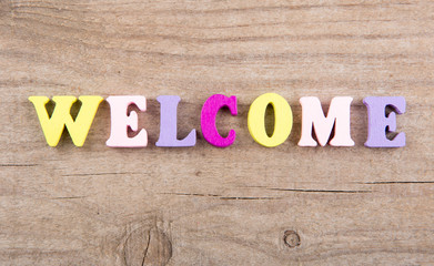 "Text ""WELCOME"" of colored wooden letters on a wooden background"