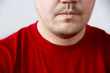 Lower half of face unshaven man in red T-shirt without emotion