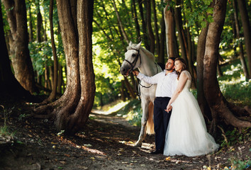 The happinest brides hold hands  in the forest