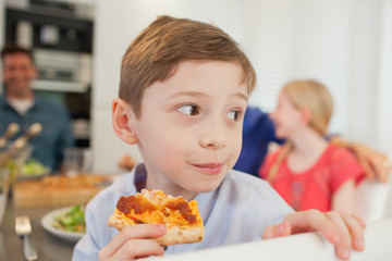 Boy eating pizza and looking away