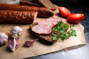 Slices of smoked sausage with spice, herbs and vegetables on the