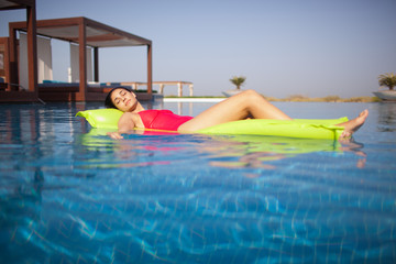 Woman relaxing on air bed in swimming pool.