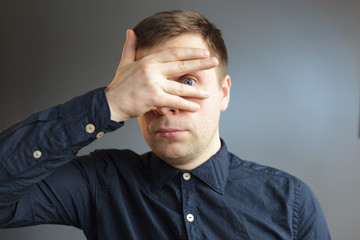 young man hides his face, covering his hands.