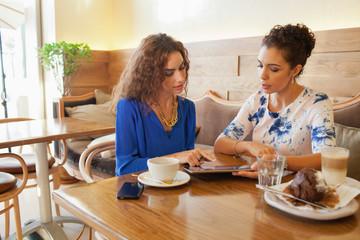 Women using digital tablet at restaurant.