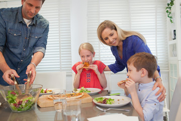 Parent with children eating pizza at home.