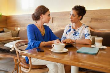 Expat women discussing at restaurant.
