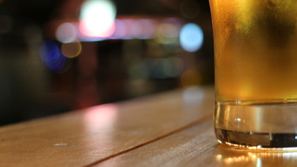 Glass of beer on table across the street from a bar. Horizontal 16:9 format.