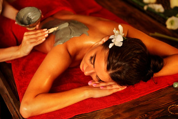 Mud mask of woman in spa salon. Back massage with clay full body . Girl on Luxary interior with candles in oriental therapy room. Top view of female with flower lying on wooden spa bed.