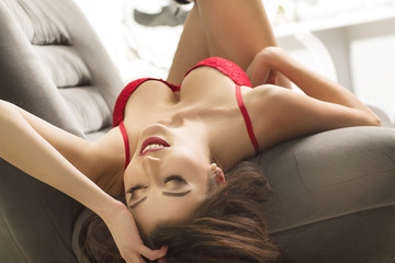 Sensual women in red lingerie lying on  the armchair