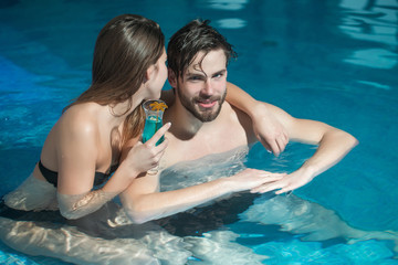 muscular man and sexy woman in blue pool with cocktail