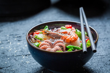 Delicious seafood noodle in dark bowl with chopsticks