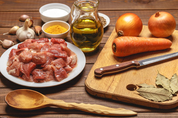 Cooking ingredients. Cutting board. Sliced raw meat, rice, oil, spices, garlic,