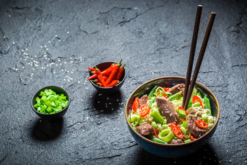 Spicy asian noodle in dark bowl with chopsticks