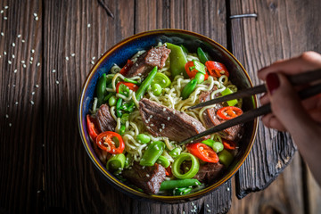Enjoy your asian noodle in dark bowl with chopsticks