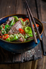 Closeup of hot noodle in dark bowl with chopsticks