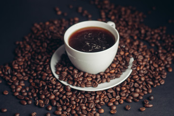 a cup of coffee with scattered coffee beans