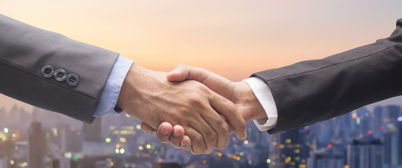 close up business man handshake fro dealing goal isolated on blurred city background,agreement financial commercial concept.