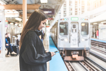 Girl with smart phone at train station in Chicago