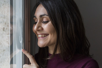 young woman smiling by the window
