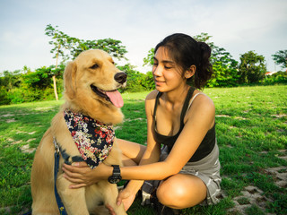 Golden retriever and Asian woman are playing in the park