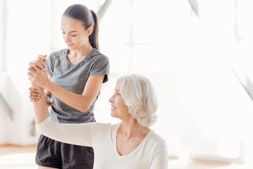 Attractive professional coach helping the elderly woman Wall mural