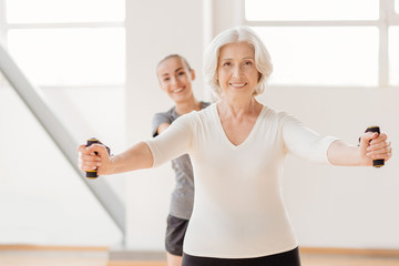 Hard working pleasant woman exercising with a resistance band Wall mural
