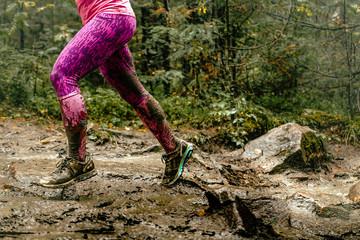 Fotomurales - woman runs over rocks in forest legs in spray dirt