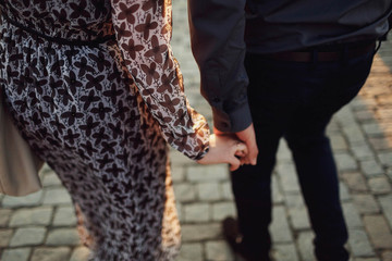 man and woman tenderly holding each other's hand