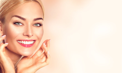 Beauty woman portrait. Beautiful spa girl touching her face and smiling. Perfect fresh skin
