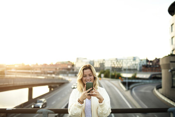 Happy young woman using mobile phone while standing on bridge against sky