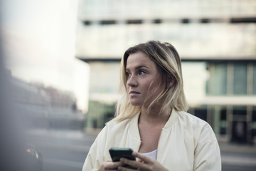 Young woman with mobile phone against building in city