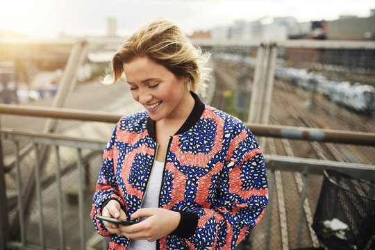 Happy woman using a mobile phone while standing on bridge